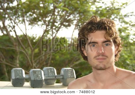 Man with weights in background