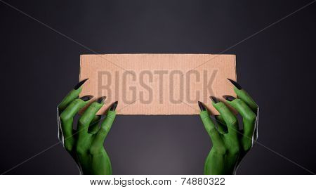 Green monster hands with black nails holding empty piece of cardboard, Halloween theme
