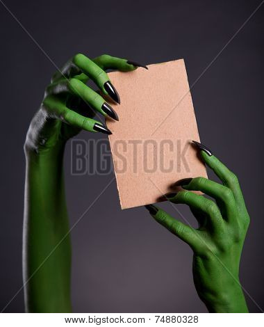 Green monster hands holding empty piece of cardboard, Halloween theme