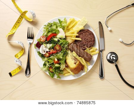 A plate filled half with unhealthy food and a stethoscope and the other half with fresh salad for a healthy diet and lifestyle. poster