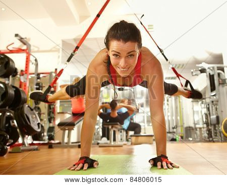 Happy woman enjoying hard suspension training in gym.