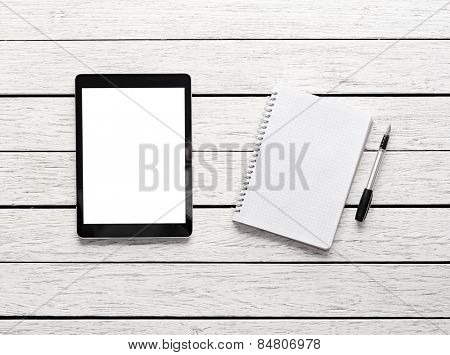 Tablet computer with notepad on white wooden desk. Clipping path included.
