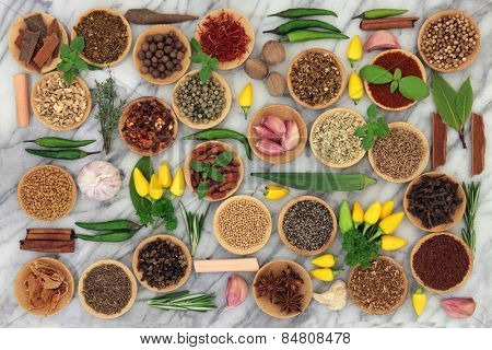 Chilli spice and herb collection in wooden bowls and loose over marble background.