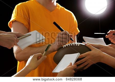 Autographs by American football star on black and lights background