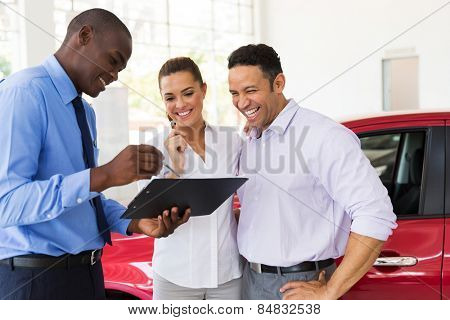 african car dealer explaining sales contract to couple buying a car