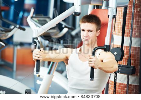 fitness man at chest pectoral muscles exercises with training weight machine station in gym