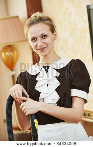 Hotel service. Portrait of female housekeeping or housemaid with vacuum cleaner at inn room