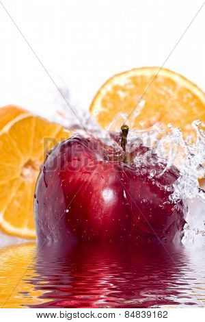 Water splashing down on an apple and orange
