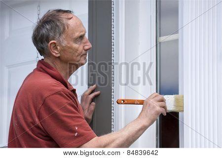 Senior man painting outside of house