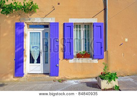 Open window and door with lavender color wooden shutters on an ocher color plastered wall on a sunny day. Bonnieux village Provence France poster