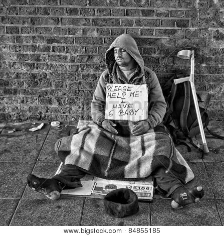 LONDON, UK - AUG 22, 2014: Homeless man with an asking for help sign sleeping in tunnel outside Waterloo train station in London in black and white.