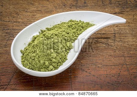 moringa leaf powder in a teardrop shaped bowl against rustic wood