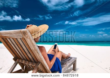Young woman in hat with mobile phone at the beach