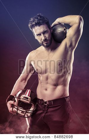 Attractive shirtless football player holding protective helmet and posing poster