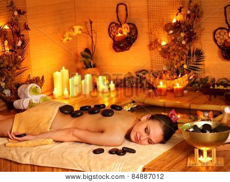 Woman getting stone therapy massage in bamboo spa. Many candles.