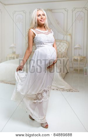 beautiful tender delicate pregnant blond woman in white dress touching her belly in white antique bedroom