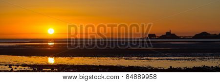 The sun rises over a wide expanse of mudflats in Swansea Bay, with the Mumbles skyline on the right.