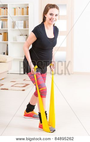 Young pregnant woman exercising with stretch band at home