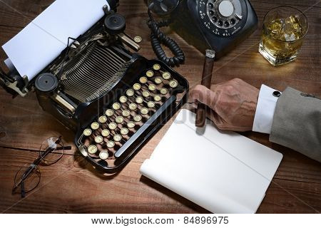 Closeup of a writer at his desk with a typewriter, rotary telephone, glass of whiskey and a cigar. A vintage feel with only the mans hand holding a cigar being shown.