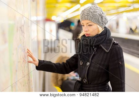 Lady looking on public transport map panel.