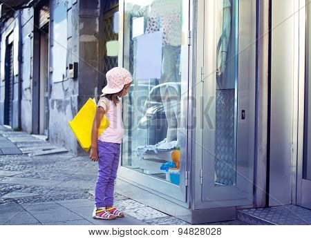 cute little girl with shopping bags walking in the city