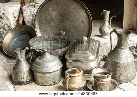 Old used retro antique metal vessels cutlery and crockery for flea market poster