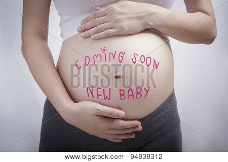Pregnancy Writing The Word Coming Soon New Baby On Stomach, Pregnancy And Newborn Baby
