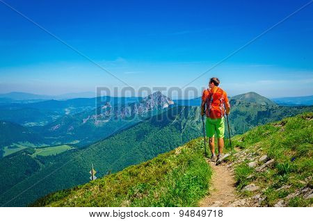 Man and orange backpack on mountain trail Slovakia