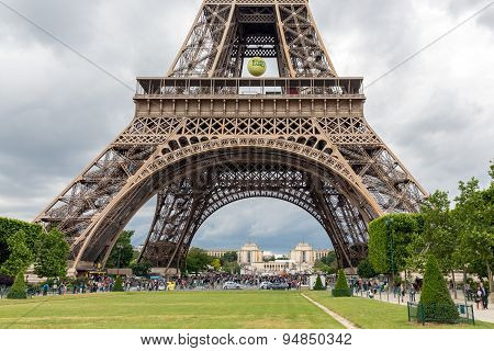 Tourists Near Eiffel Tower With Big Tennis Ball Of Roland Garros In Paris, France