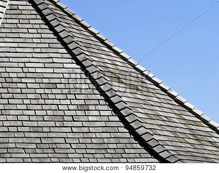 Weathered Cedar shingles on roof - blue sky background