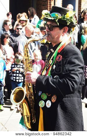 Man plays saxophone in a parade