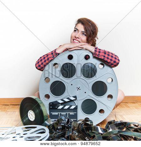 Young smiling woman sits on wooden floor behind big original cinema movie reel and filmstrip poster