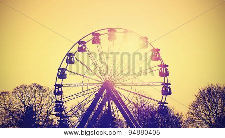 Retro Instagram Toned Silhouette Of Ferris Wheel At Sunset.