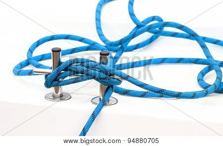 Yacht bollard (bitt) with blue tangled rope on a deck concept picture. poster