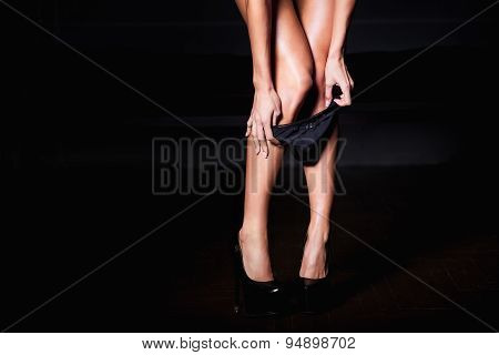 Beautiful woman with sexy legs taking of her black panties in erotic way. poster