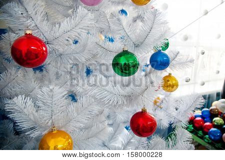White Christmas tree decorated with colored Christmas balls and a box with balls in the background