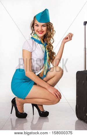 The young beautiful stewardess holds baggage on a white background