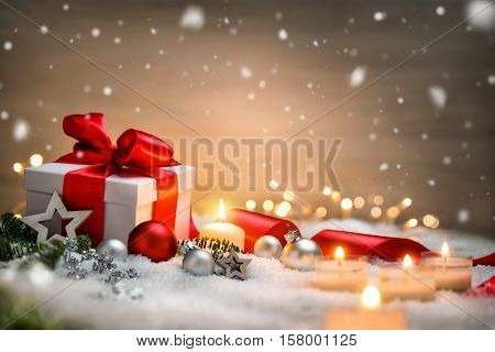 Christmas scene with a white gift box red bow and ribbon candles lights baubles fir branches and snow with copy space