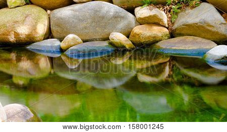 Calm Small lake with rocks on the shore reflecting on cristal water