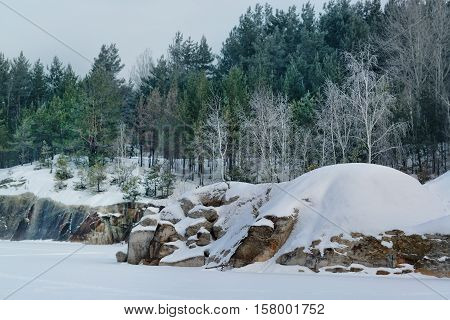 Winter on the lake with rocks and forest
