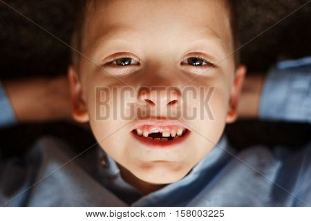 Portrait little boy in fall missing his first milk tooth