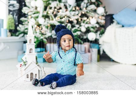 Cute little baby child boy in blue hat sitting at a home interior and waiting Santa on background of the modern Christmas tree with gifts.