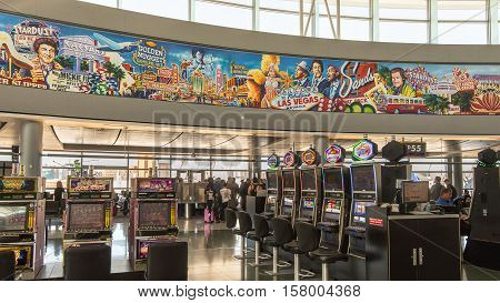 LAS VEGAS NV/USA - NOVEMBER 7 2016: Passengers and slot machines at McCarran International Airport terminal below a mural depicting the The Rat Pack Dean Martin Sammy Davis Jr. Frank Sinatra and the Stardust Caesar's Palace and Golden Nugget casinos.