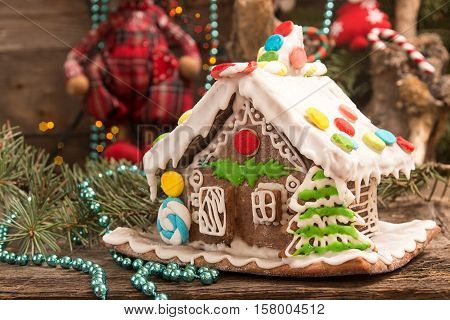 Christmas Gingerbread House And Holiday Decorations On Old Wooden Table