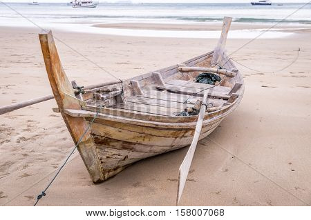Wooden longtail boat sitting on Ao Kantiang beach at low tide in Ko Lanta, Thailand