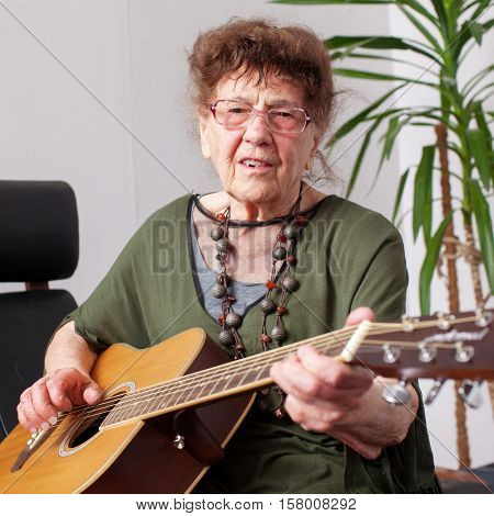90 year old grandmother to play the guitar. Elderly woman at home. Mature female hobbies