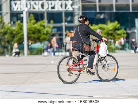 La defense France - April 09 2014: woman ride a bike in town. Alternative ecological clean transport in a city