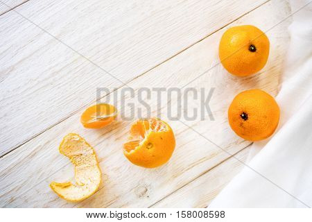Whole and peeled tangerines on white boards