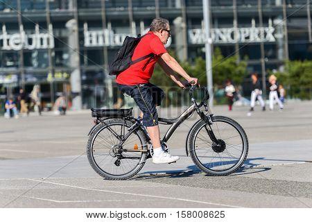 La defense France - April 09 2014: Man ride a bike in town. Alternative ecological clean transport in a city