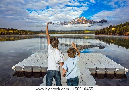 Two boys stand on the plastic dock for motor boats. Cumulus clouds over the Pyramid mountain and Pyramid Lake